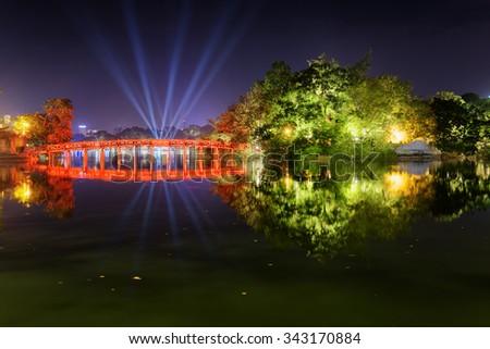Night view of the Huc Bridge (Morning Sunlight Bridge) to the Jade Island on the Hoan Kiem Lake (Lake of the Returned Sword) in historic centre of Hanoi, Vietnam. The bridge reflected in the lake. - stock photo