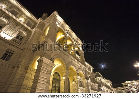 Night view of the Palace of Government of the city of Trieste, with the moon in the background - stock photo