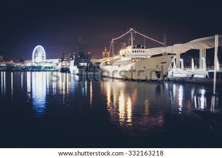 Night view of the port of Malaga. Big cruises ships and ferris wheel in the background. Vintage style. - stock photo