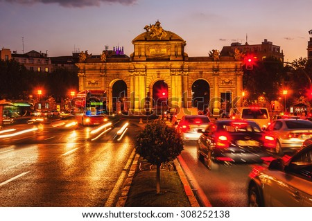 Night view of The Puerta de Alcala at sunset - a monument in the Independence Square in Madrid, Spain. Motion blurred cars and buses, illumination and lights, violet sky - stock photo