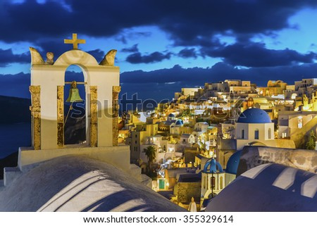 Night view of the romantic bell tower of the Orthodox Church and the village of Oia with beautiful illumination in blurred streets and houses in the background.Santorini(Thira) island.Greece.Europe. - stock photo