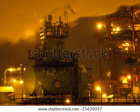 Night view of the vapors flowing over a petrochemical processing facility, 440 kms to the south of Fort McMurray's oil sands in Edmonton, Alberta.  The site lighting gave this photo its yellowish hue - stock photo