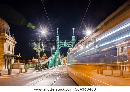 Night view of tram on Liberty Bridge (Freedom Bridge) with lens flares in Budapest, Hungary. - stock photo