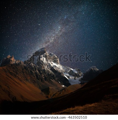 Night view of Ushba mountain with dark starry sky. Beautiful outdoor scene in the Caucasus mountains, Upper Svaneti, Europe.