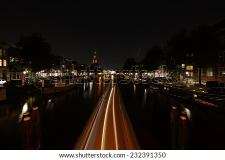 Night view on the Amsterdam canal at night with boat lighting trails in Holland - stock photo