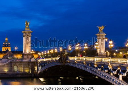 NIght view on the famous landmark Alexander iii bridge in Paris, capital of France, with characteristic street lights lighting the bridge and the dome of les invalides - stock photo