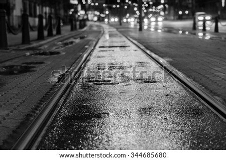 Night view on wet tram rails after rain. Blurred traffic lights on background, black and white tone - stock photo