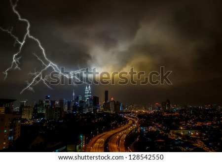 Night view scenery at the busy highway in Kuala Lumpur city with storm cloudy and lightning - stock photo