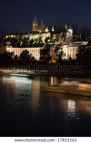 Night view to Lesser Town and Prague castle over Vltava river with boat.