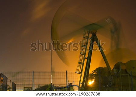 Night viewof an oil pump illuminated by flares of an refinery plant - stock photo