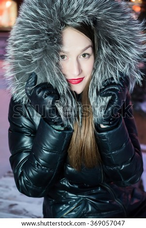Night winter city portrait of the young attractive woman in warm cloth