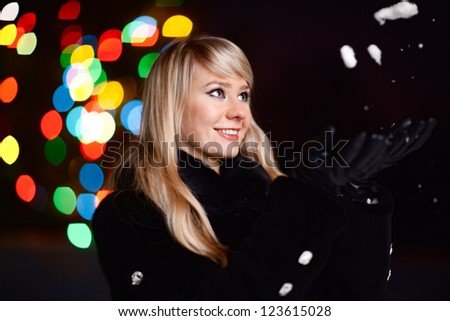Night winter portrait of a pretty young lady with a Christmas tree lights on background - shallow DOF, focus on eyes - stock photo
