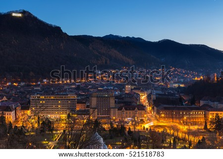 Night wintry cityscape with city lights of Brasov city, Romania.