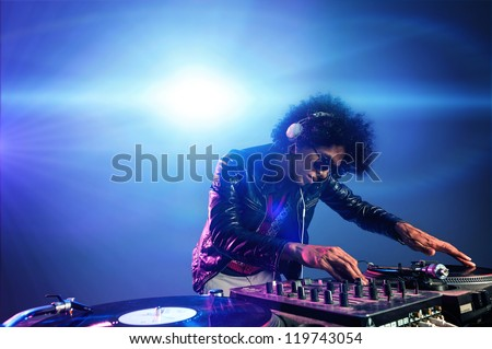 nightclub dj playing music on deck with vinyl record headphones light flare clubbing party scene - stock photo