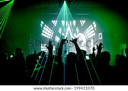 Nightclub man with mobile phone recording lasers at party rave silhouette - stock photo
