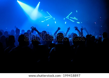 Nightclub party crowd with hands in the air