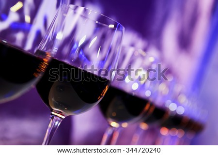 Nightclub wine glasses with red wine lit by party festive lights on dark-purple background, nightlife - stock photo