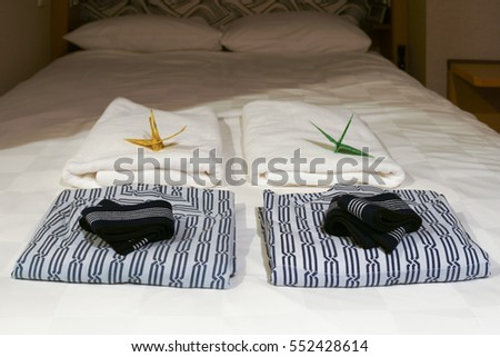 Nightgowns and towel on white bed in Luxury Japanese hotel room.