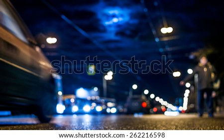 Nightlife, man catches a taxi voting on the sidelines at moonlit night. In blue tones - stock photo