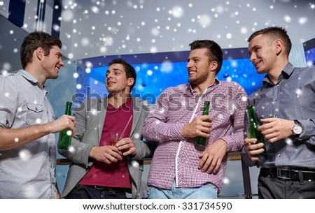 nightlife, party, friendship, leisure and people concept - group of smiling male friends with beer bottles drinking in nightclub and snow effect