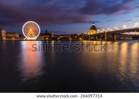 Nightly view of a spinning ferris wheel in Toulouse - stock photo