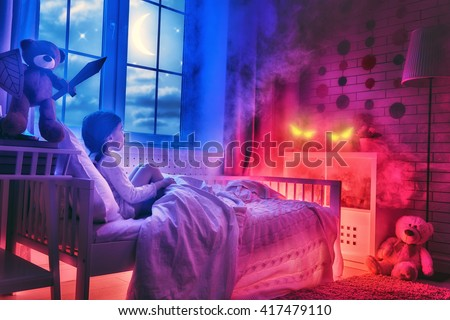 Nightmare for children. Little child girl is afraid of monsters in the dark of night. Frightened little girl and her teddy bear friend are protected against monsters. - stock photo