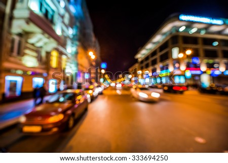 Nights lights of the big city, cars go down the avenue past the bright shop windows. Wide-angle view, defocused image