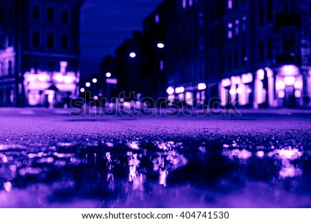 Nights lights of the big city, the empty night crossroad between buildings. Close up view of a puddle level, image in the purple-blue toning - stock photo