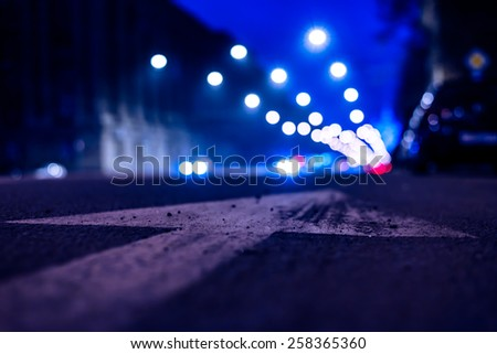 Nights lights of the big city, the night avenue with arrow and headlights of the approaching cars, close up view from asphalt level. In blue tones - stock photo