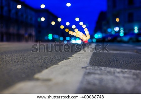 Nights lights of the big city, the night avenue with headlights of the driving cars. Close up view from the level of the dividing line