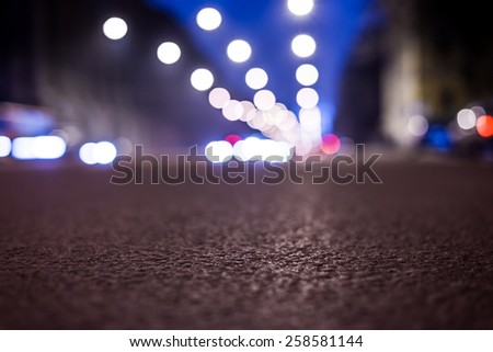 Nights lights of the big city, the night avenue with lanterns, close up view from asphalt level. In blue tones - stock photo