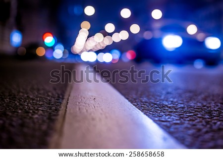 Nights lights of the big city, the night avenue with road markings and headlights of the approaching car, close up view from asphalt level. In blue tones - stock photo