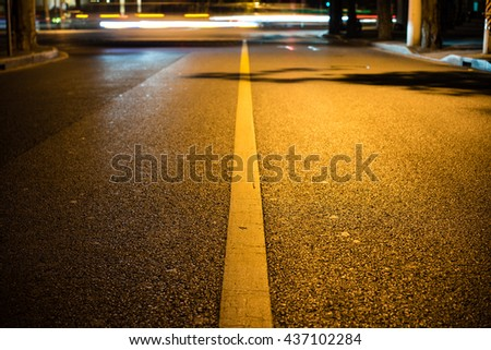 Nights lights of the big city, the night avenue with road markings and headlights of the approaching cars, close up view from asphalt level.