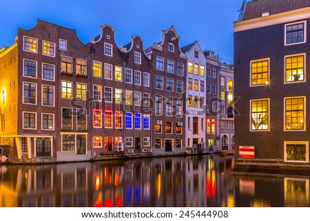 Nightscape of colorful traditional canal houses at night seen from the armbrug on the oudezijds voorburgwal in the UNESCO World Heritage site of Amsterdam - stock photo