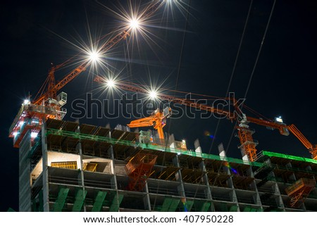 Nighttime and crane working with building construction in city - stock photo