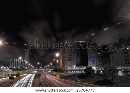 Nighttime highway traffic in downtown district - stock photo