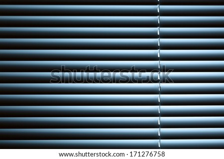 Nighttime privacy - closed venetian blinds or shutters with blue back light.