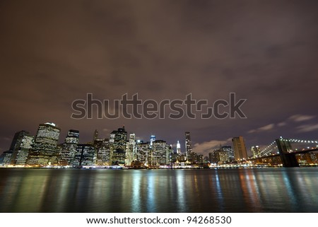 Nighttime view of Lower Manhattan skyline with Brooklyn Bridge in New York City - stock photo