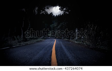 Nighttime with curvy roadway in forest at national park. Landscape of moonlight in a beautiful green forest. Outdoors. The moon taken with my own camera, no NASA images used. - stock photo