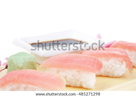 Nigiri Sushi - Set of Nigiri sushi topped with raw Tuna (maguro) . Isolated over white background . on wooden board