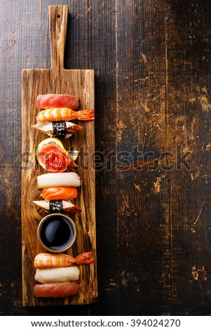 Nigiri Sushi set on serving board on wooden background - stock photo