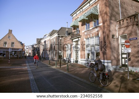NIJKERK, NETHERLANDS, 24 NOVEMBER 2014: street with people on bicycle in the dutch town of Nijkerk
