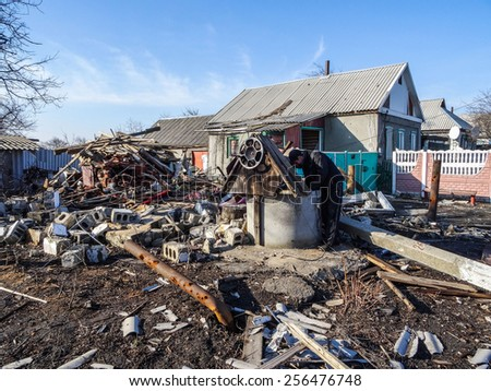 NIKISINO, UKRAINE - Feb 27, 2015: Man tries to save part of the assets in the ruins of his house. Village Nikishino located 20 km from Debaltseve, Ukrainian military was abandoned three days ago.