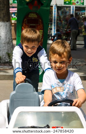 NIKOLAEV, UKRAINE - June 21, 2014: Kids in the play area riding a toy car - stock photo
