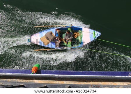 NILE RIVER, EGYPT - FEBRUARY 3, 2016: Men in a row boat tied to the side of a Nile River Cruise ship trying to sell scarves to the passengers in Egypt