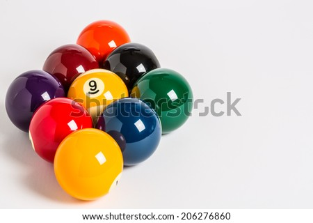 Nine Ball racked in a diamond shape on a plain white background left side with cue stick, chalk and cue ball in foreground.  - stock photo