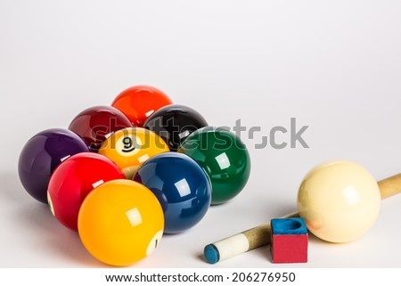 Nine Ball racked in a diamond shape on a plain white background left side with cue stick, chalk and cue ball ion foreground.  - stock photo