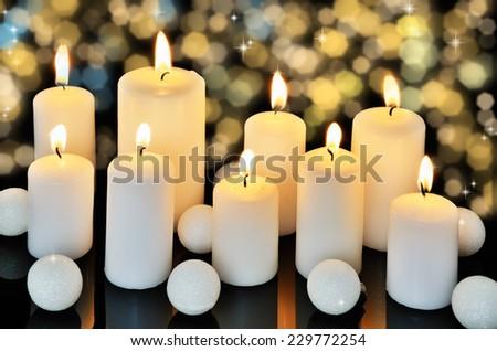 nine burning candles on a dark shiny background horizontal - stock photo