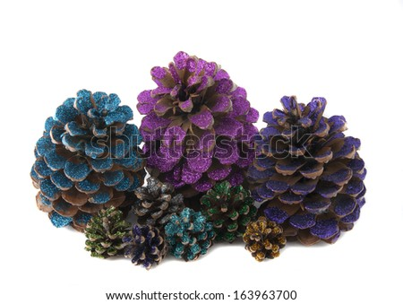 nine christmas pinecones painted with colored glitter - stock photo