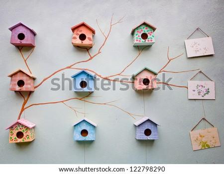 Nine cute little bird house on paint wall - stock photo